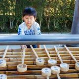 Un enfant utilise le plongeur de l'eau au temple de Todaiji à Nara Image libre de droits