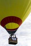 Un enlèvement jaune et d'un rouge ardent de ballon à air Image libre de droits