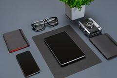 Un ensemble d'accessoires noirs de bureau, verres, fleur et futé verts sur le fond gris Photos libres de droits