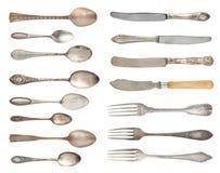 Un ensemble d'argenterie fine antique Cuillères, fourchettes et couteaux de cru d'isolement sur un fond blanc images stock