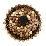 Un ensemble de bonbons au chocolat délicieux, encadré avec des grains de café sur un fond blanc Image stock