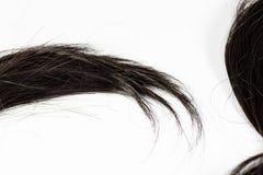 Un ensemble de prolongements de cheveux noirs des cheveux bouclés de brune rougeâtre sur une table de boutique de beauté photographie stock