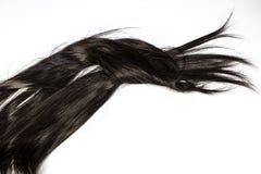 Un ensemble de prolongements de cheveux noirs des cheveux bouclés de brune rougeâtre sur une table de boutique de beauté photographie stock libre de droits