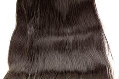 Un ensemble de prolongements de cheveux noirs des cheveux bouclés de brune rougeâtre sur une table de boutique de beauté images libres de droits