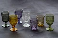 Un ensemble de transparent, verres cristal de différentes couleurs, sur une table en bois foncée Images libres de droits