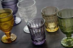 Un ensemble de transparent, verres cristal de différentes couleurs, sur une table en bois foncée Photographie stock