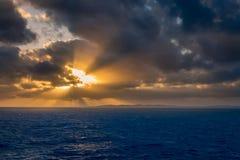 Un ensemble dramatique de nuages dérivant au-dessus des eaux tropicales de la mer des Caraïbes sont allumés par les derniers mome Images stock