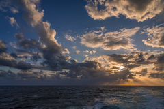 Un ensemble dramatique de nuages dérivant au-dessus des eaux tropicales de la mer des Caraïbes sont allumés par les derniers mome Photo libre de droits