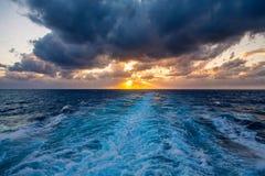 Un ensemble dramatique de nuages dérivant au-dessus des eaux tropicales de la mer des Caraïbes sont allumés par les derniers mome Photographie stock