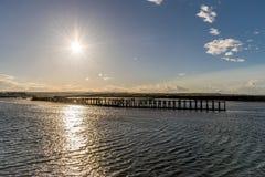 Un ensemble du soleil avec des rayons d'étoile établissement au-dessus d'une jetée et d'une mer images libres de droits
