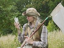 Un entomólogo de la mujer joven se vistió en estilo rural, con una red del insecto y una botella de la matanza imagen de archivo