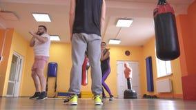 Un entraîneur de boxe forme un homme et une fille dans un gymnase où des sacs de sable sont accrochés, mouvement lent banque de vidéos