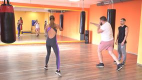 Un entraîneur individuel d'arts martiaux enseigne un homme et une boxe de fille et une autodéfense, sportif, Caucasien clips vidéos