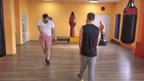 Un entraîneur individuel d'arts martiaux enseigne un homme et une boxe de fille et une autodéfense, sportif banque de vidéos