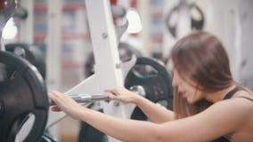 Un entrenamiento de la mujer del atleta en el gimnasio - ponga el dumbell en el suelo y limpia hacia fuera el sudor de la frente almacen de metraje de vídeo