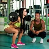 Un entrenamiento de los pares de la aptitud - mann y la mujer aptos entrenan en gimnasio Fotos de archivo