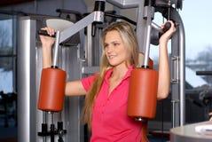 Un entrenamiento rubio joven de la mujer en una gimnasia de la aptitud Foto de archivo