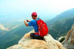 Un entusiasta del alpinismo toma una foto del teléfono celular en el borde del acantilado del pico de montaña del ` s Shaolin de  foto de archivo libre de regalías