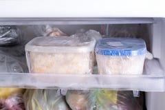 Un envase con la comida en el congelador Un congelador embaló con el pollo, la sopa y la diversa comida congelada fotos de archivo libres de regalías