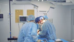 Un equipo de cirujanos está realizando una operación en una unidad de hospital almacen de metraje de vídeo