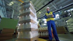 Un equipo de embalaje funciona mientras que un hombre que lo comprueba en una fábrica metrajes