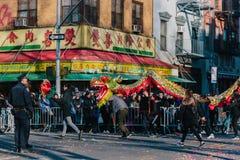 Un equipo de la danza del dragón que viaja en el desfile lunar del Año Nuevo en Chinatown, Manhattan foto de archivo libre de regalías