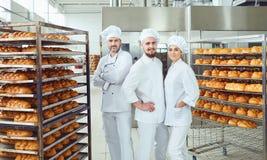 Un equipo de sonrisas de los panaderos en la panader?a fotos de archivo libres de regalías