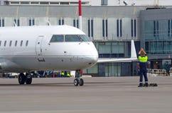 Un equipo de tierra del regulador del tráfico del aeropuerto que dirige un aeroplano en una pista del aeropuerto imagenes de archivo