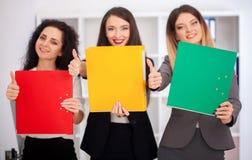 Un equipo de trabajadores hermosos jovenes con las carpetas coloridas en su Foto de archivo libre de regalías