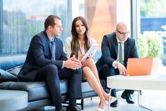 Un equipo del negocio de tres que se sientan en oficina y trabajo de planificación LOS E.E.U.U. imagenes de archivo