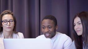 Un equipo internacional del negocio de tres personas en el ordenador portátil está hablando almacen de video