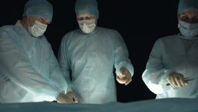 Un equipo quirúrgico actuar encendido a un paciente durante procedimiento Médico con los tejidos pacientes de los cortes del esca almacen de video