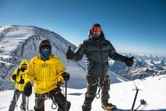 Un escalador de mediana edad en abajo una chaqueta y un arnés muestra un pulgar para arriba al lado de sus amigos en la manera al Fotos de archivo