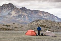 Un escalador de montaña y dos tiendas en un campo bajo remoto en el Blanca de Cordillera Fotos de archivo