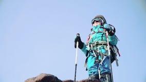 Un escalador en un traje brillante se coloca en el top de la montaña y aumenta sus manos con los polos de esquí para arriba y fel almacen de metraje de vídeo