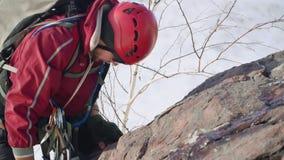 Un escalador experimentado con la barba se alza un escarpado y la roca aguda, superando dolor y cansancio se está arrastrando par almacen de metraje de vídeo