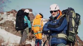 Un escalador experimentado con una barba gris y los vidrios que se colocan con los brazos cruzados en su pecho y que disfrutan de metrajes