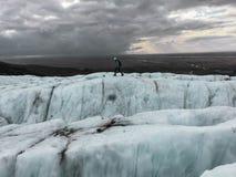 Un escalador que camina a través de los glaciares islandeses imagenes de archivo