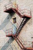 Un escalier de secours rouge en métal contre le doo bleu-foncé Photos libres de droits