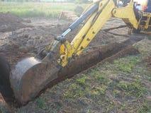Un escavatore del lavoro scava una fossa in una casa di campagna immagini stock