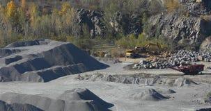 Un escavatore giallo carica il granito in una cava, un granito dei carichi dell'escavatore in un autocarro con cassone ribaltabil archivi video
