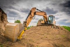 Un escavatore giallo sul lavoro fotografie stock