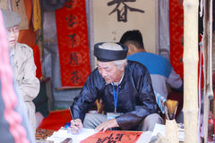 Un escolar escribe caracteres chinos de la caligrafía en el templo de la literatura Fotografía de archivo libre de regalías