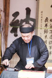 Un escolar escribe caracteres chinos de la caligrafía en el templo de la literatura Imagen de archivo