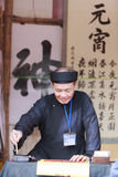 Un escolar escribe caracteres chinos de la caligrafía en el templo de la literatura Imagenes de archivo