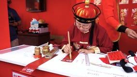 Un escolar escribe suerte y felicidad en caracteres chinos de la caligrafía almacen de video