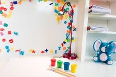 Un escritorio de la escuela del ` s del niño con las fuentes de escuela, la pintura colorida, y un juguete azul relleno del elefa imagen de archivo