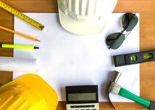Un escritorio de trabajo del arquitecto con las herramientas y casco de seguridad con el espacio de la copia imagen de archivo libre de regalías