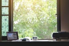 Un escritorio del trabajo con una atmósfera natural fuera de la ventana con el sol de la mañana foto de archivo