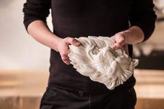 Un escultor lleva a cabo en sus manos la cabeza de un león hecho del yeso Trabajo sobre la escultura en el taller del yeso imagen de archivo libre de regalías